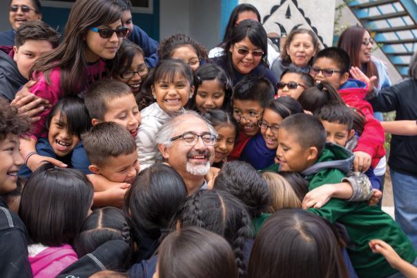 Principal Antonio Trujillo gets a surprise hug from student at St. Joseph Mission School