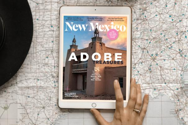A hand is seen tapping an iPad, featuring a cover image from New Mexico Magazine. The image is an adobe church.