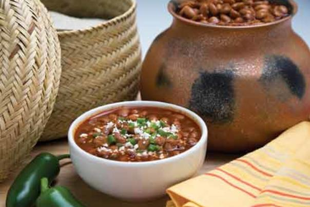 Bowl of beans in front of a clay pot of beans