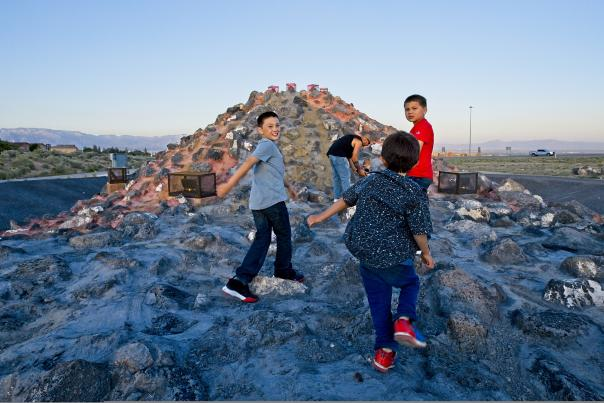 Family members hike up the manmade volcano on Albuquerque's west side, New Mexico Magazine