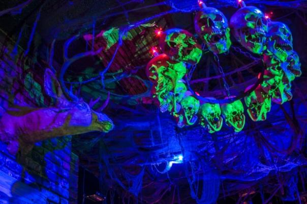 A Skull Chandelier glows under blacklight at an Oakland-area Halloween event.