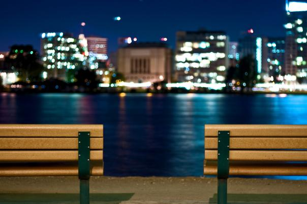 Lit benches overlooking city and body of water at night.