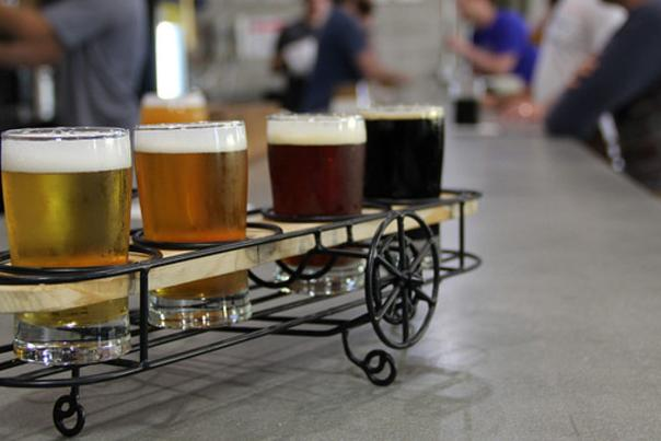 A flight of beer samples displayed apropros in wire-framed bi-plane-shaped holder at Crooked Can Brewing. Flight sits on bar with people in background.