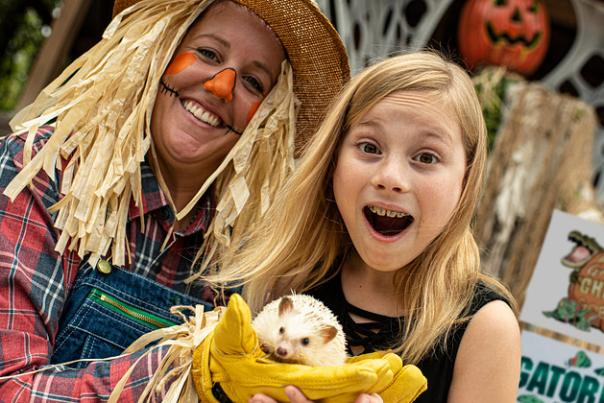 Scarecrow with a girl at Gatorland's Gators, Ghosts and Goblins Halloween event