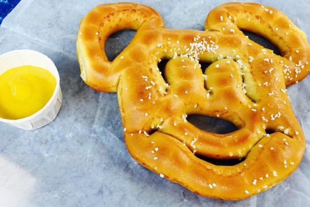 Miriam Porter, writer, and son, Noah eat a hot pretzel at a Disney restaurant