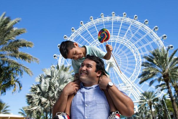 A boy on top of his dad's shoulders, while smiling and holding a lollipop, in front of The Wheel at ICON Park