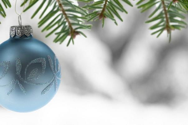 A blue Christmas ornament hanging on a pine tree