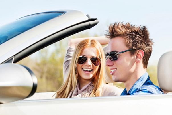 Young couple sitting in their car and enjoying in the road trip.