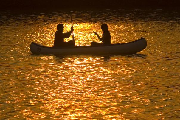 Two people in a canoe at sunset