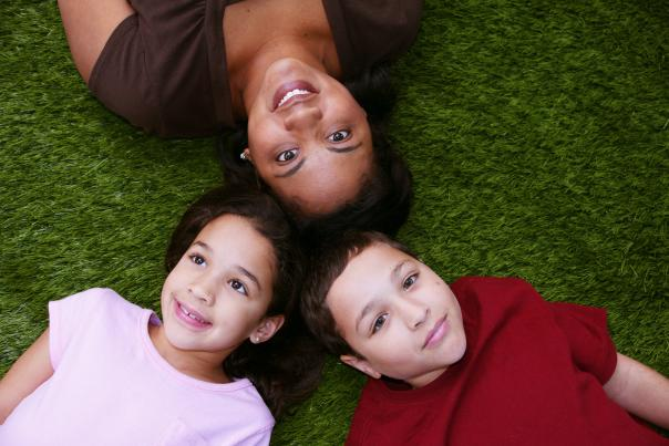 Hispanic mother and her two kids laying on the ground