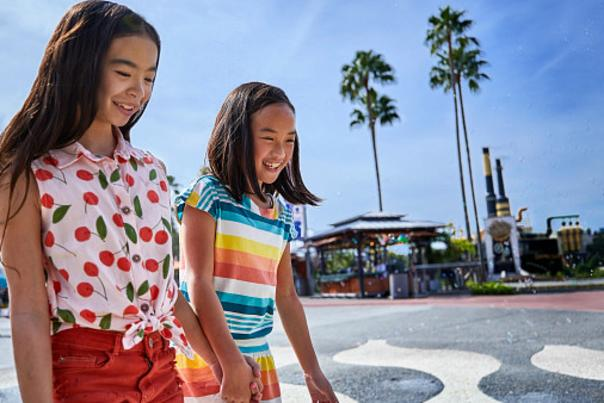 Two girls walking across a splash pad at Universal Citywalk Orlando
