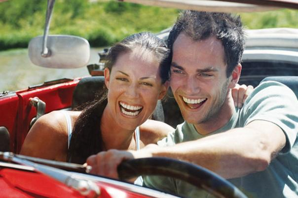 A couple driving in a red convertible