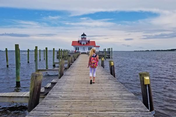 A woman walks on the boardwalk toward the Roanoke Marshes Lighthouse in the Outer Banks