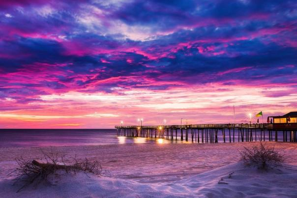 An illuminated boardwalk under a striking sunset in the Outer Banks