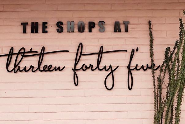 """Image of a pink brick wall with """"The Shops at Thirteen Forty Five"""" in black font"""