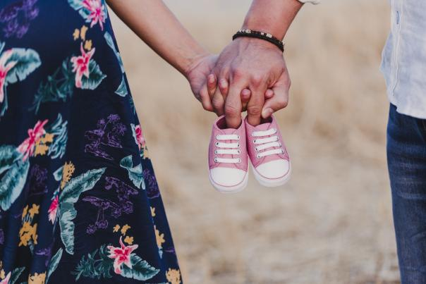 Pregnant couple holding baby shoes