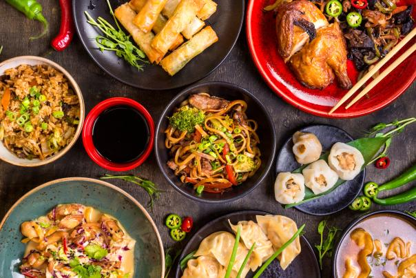 Spread of different Chinese food on black table.