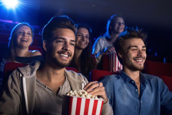 Gay men enjoying popcorn while sitting in a movie theater