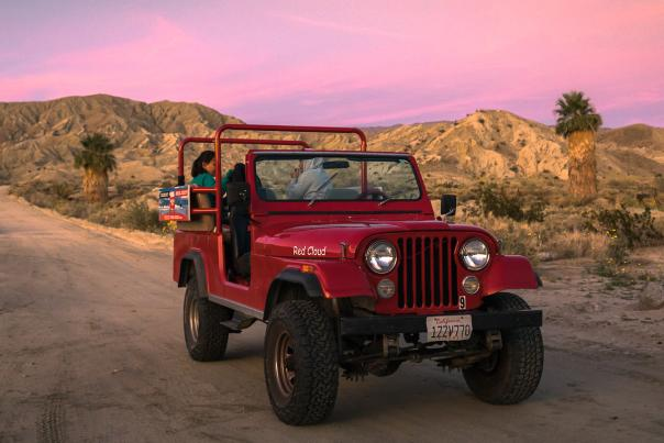 Desert Adventures Red Jeep Tour at sunset on a dirt road.