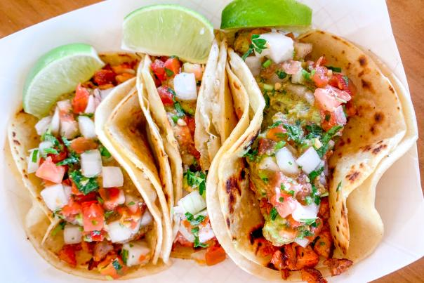 An overhead view of three street tacos topped with limes and pico de gallo.