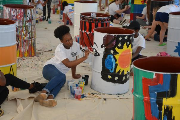 Image of a young lady painting the solar system on a recycled barrel.