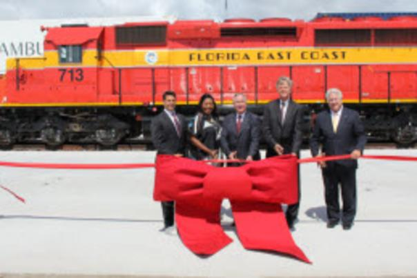 image of ribbon cutting ceremony at ICTF with train engine in the background.