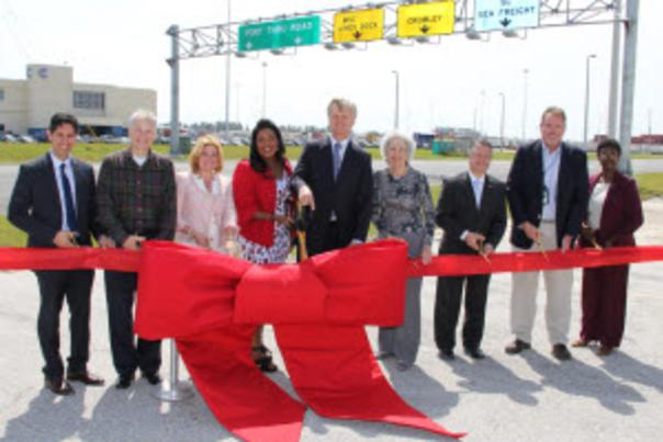 Image of Port, County and State official cutting a red ribbon to open McIntosh Road.