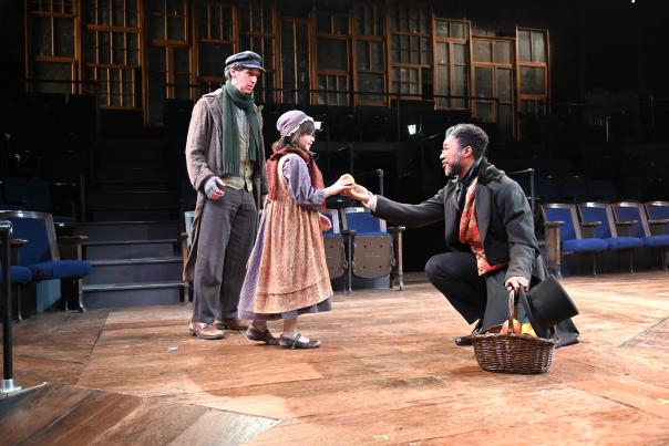 Scrooge giving food to a young girl and her father
