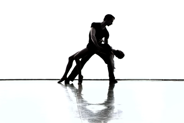Man and woman wearing all black dancing in front of a white background.