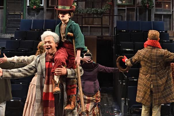 A Christmas Carol live performers on stage with their arms held out