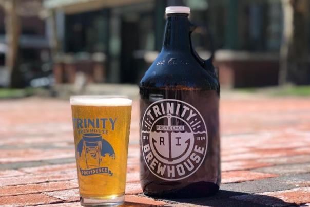 Trinity Beer Garden Pint Glass Next To A Growler