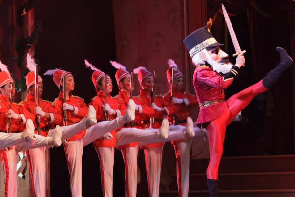 Toy soldiers played by children are lined up on stage behind a man in a nutcracker costume.