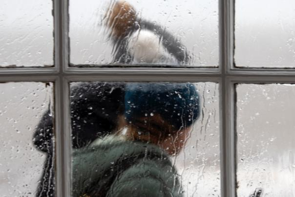 A man and a woman wearing winter hats walking by a window in the rain.