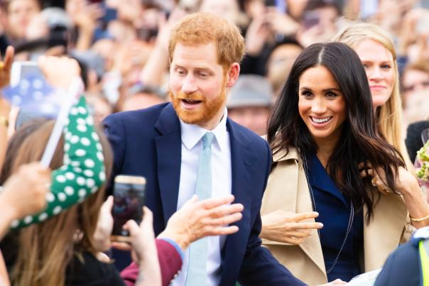 Prince Harry, Duke of Sussex and Meghan Markle, Duchess of Sussex, in a crowd holding Del's Lemonade