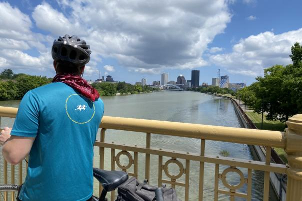 Cyclist looking out at Rochester skyline from Ford Street Bridge
