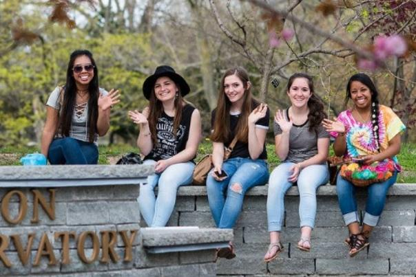 A group of young women wave hello to the camera at the Rochester Lilac Festival