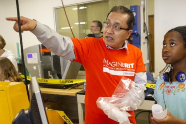 teacher instructions young student in science lab at Imagine RIT in Rochester, NY