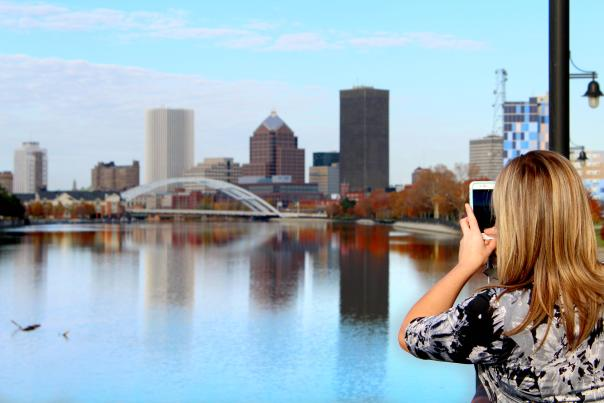 Woman takes a photo of the Rochester fall skyline