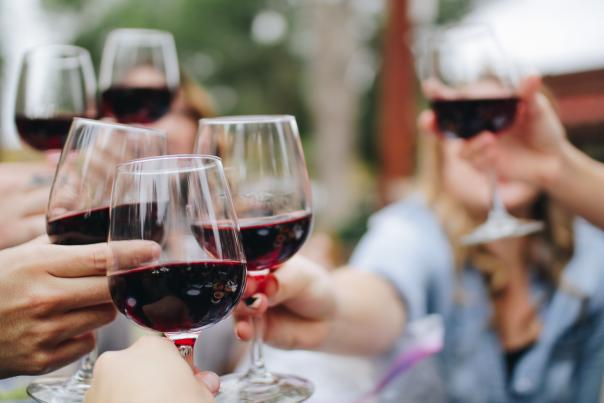 Group of friends celebrating and cheering with glasses of wine
