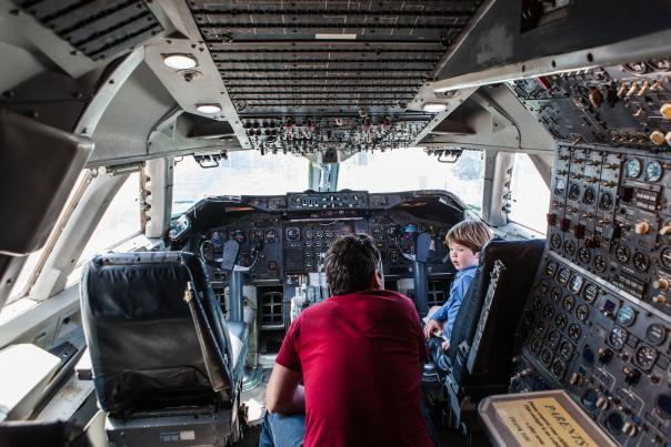 Kid experiencing the flight deck at Hiller Aviation Museum with a tour guide