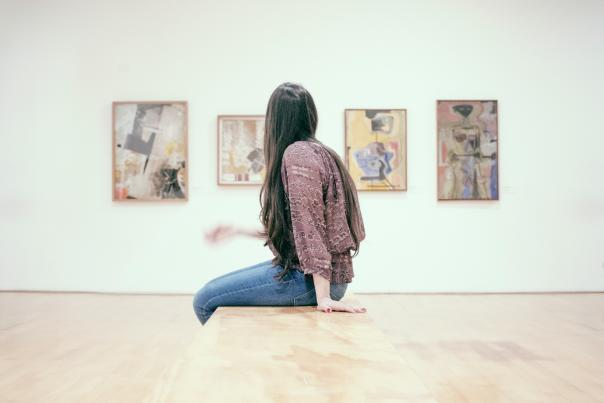 Woman sitting on the bench at an Art Museum admiring beautiful paintings on the wall