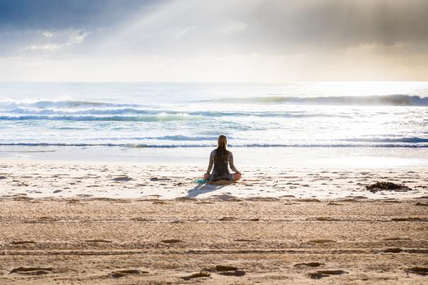 Woman relaxing at the beach practicing meditation