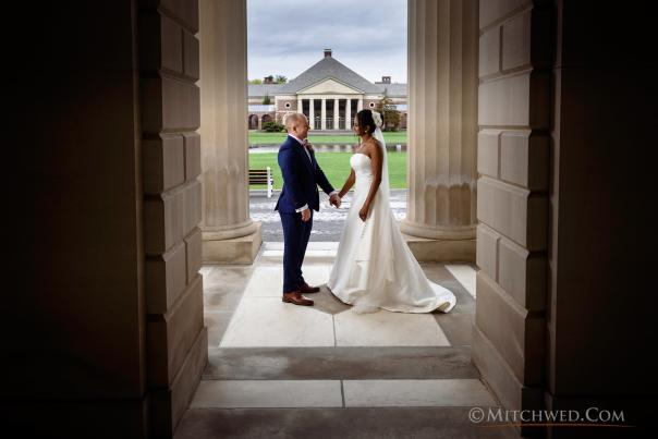 Couple holding hands in front of Saratoga Hall of Springs during wedding