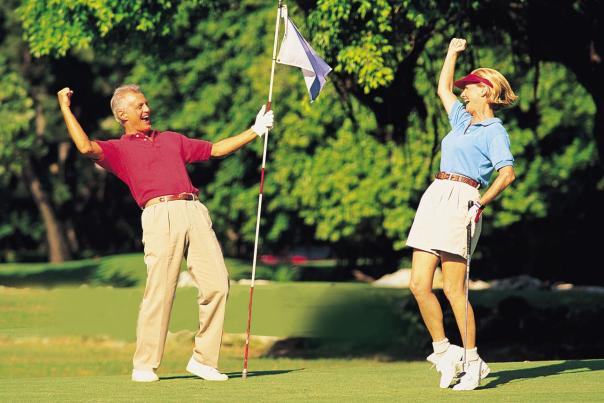 Man holding the flag by the hole on the course, and he is cheering with a woman