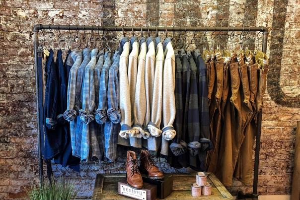 Union Hall rack of mens' shirts with rolled cuffs against an exposed brick wall with shoes displayed underneath