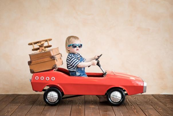 Toddler in child-sized red car, wearing sunglasses with suitcases