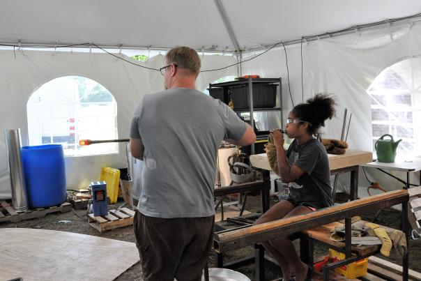 Gregory Tomb helping a young girl blow glass in his tented studio at the Gideon Putnam