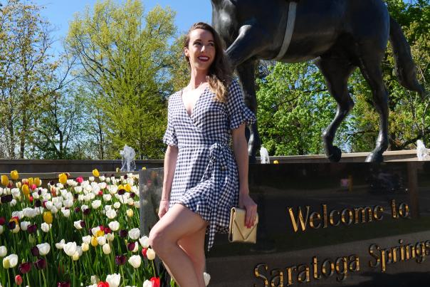 Woman leaning against Saratoga Springs Native Dancer with Tulips in the background