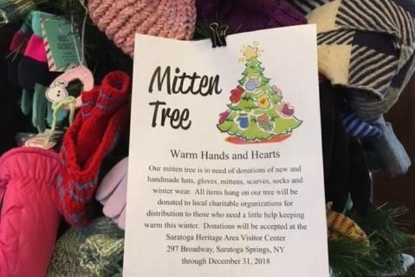 Tree of hats and mittens with Mitten Tree sign and description