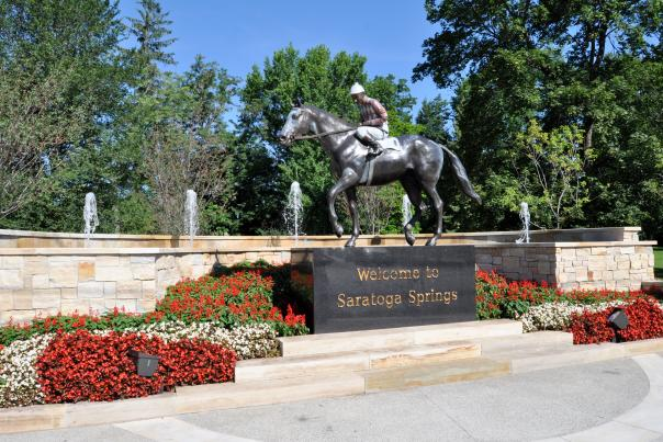 Native Dancer statue surrounded by summer flowers with fountains behind it.